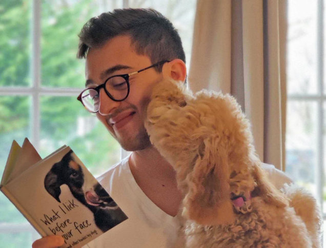 Dog licking person's face with book