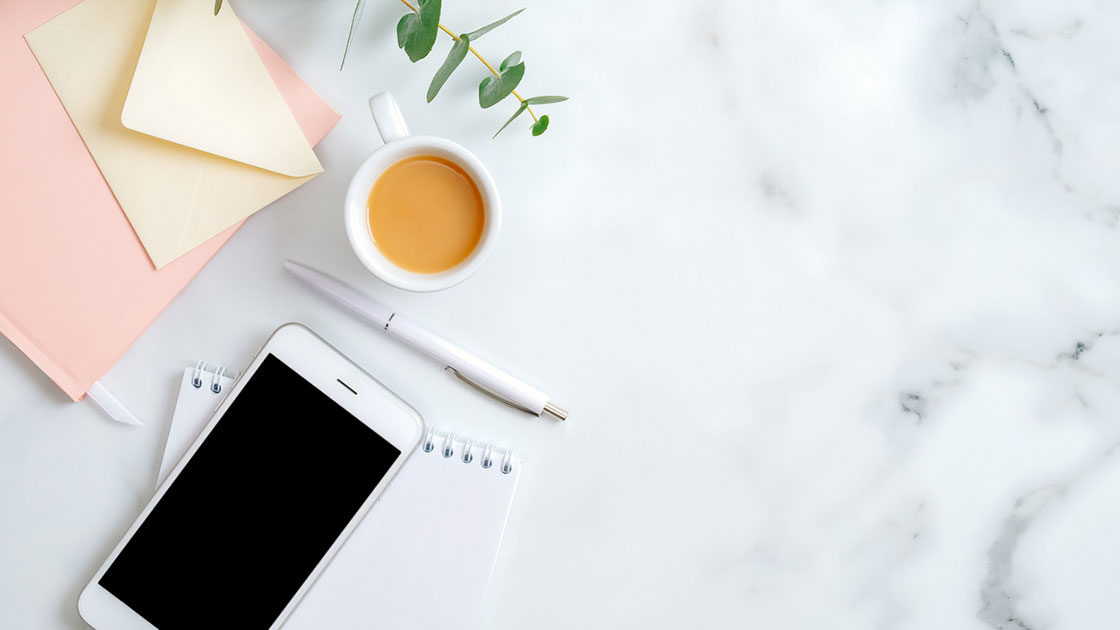Phone on marble desk with coffee