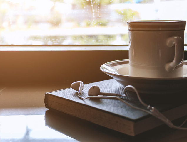 Headphones and coffee resting on a book
