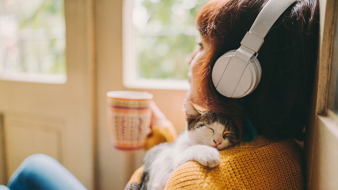Person listening to headphones with cat