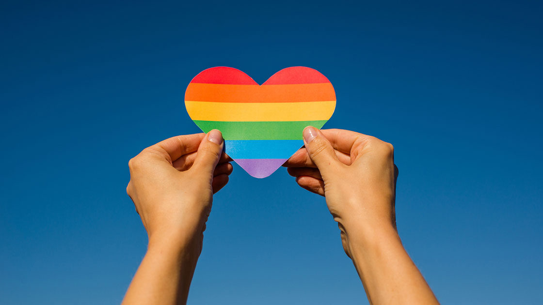 Hands holding up a rainbow lgbtq heart