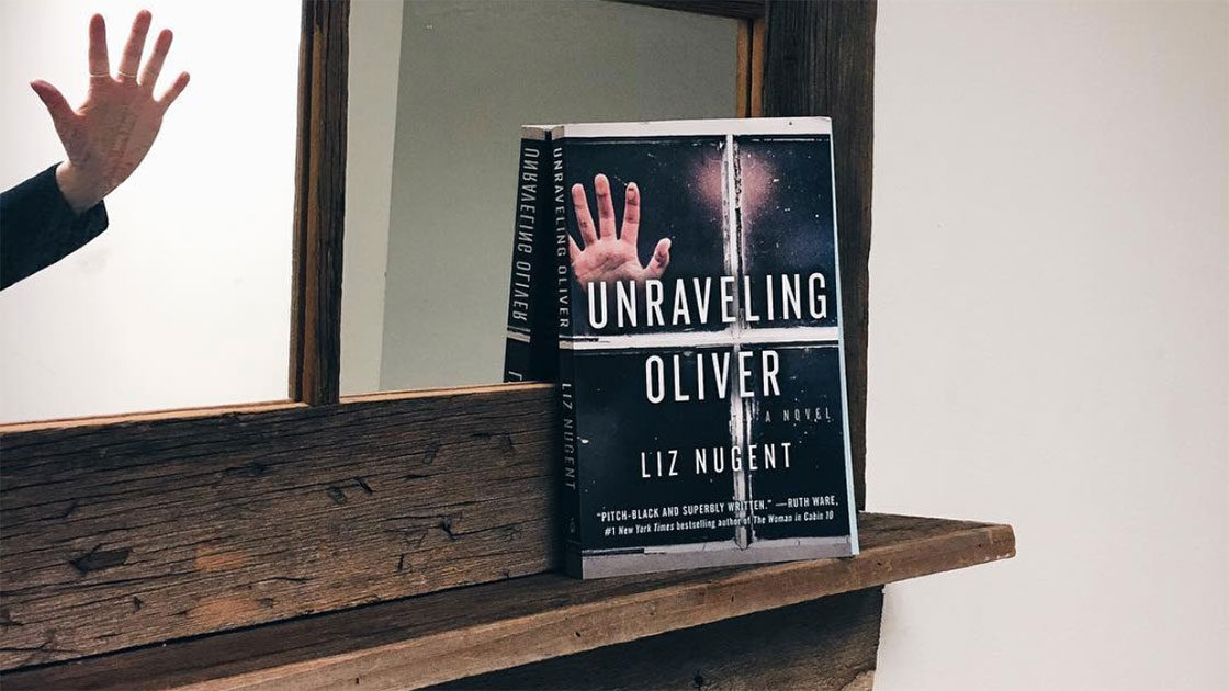 Unraveling Oliver book with hand against window